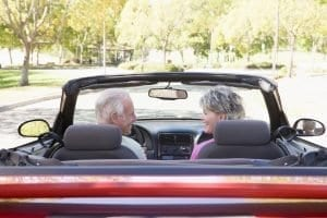 couple sitting in a convertible after using retirement calculators